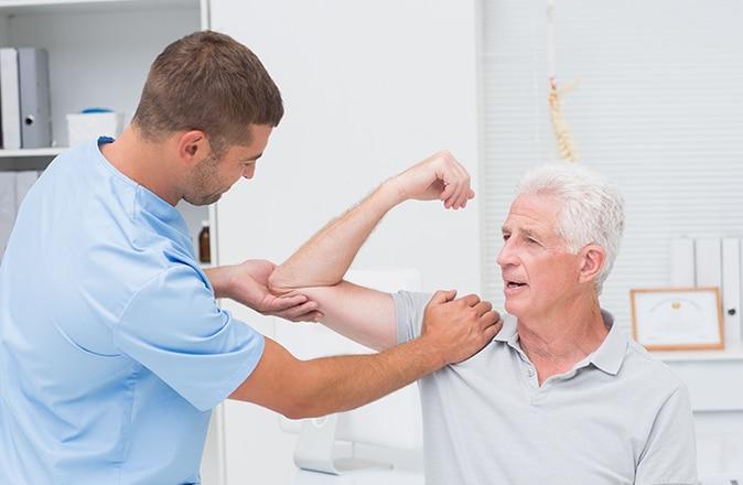 Man met symptomen van artrose wordt gecontroleerd door een arts.