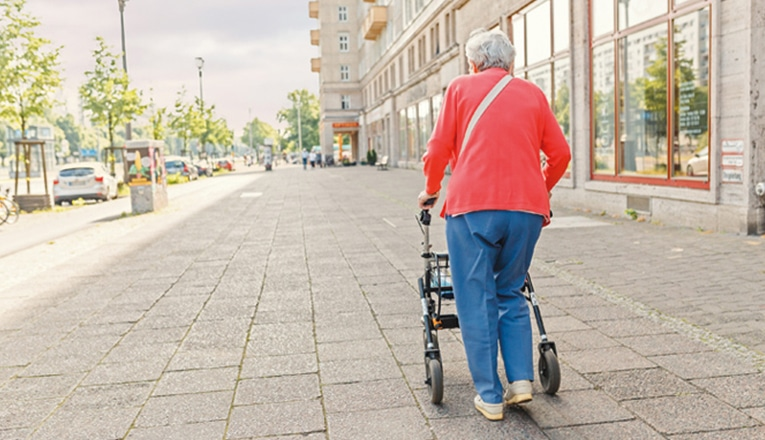 Eenzame vrouw loop over straat achter haar rollator