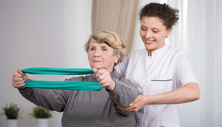 Mevrouw doet oefeningen met een fysiotherapeut tegen een rughernia.
