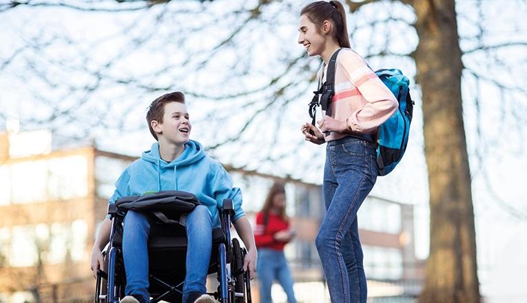 Jongen met duchenne zit in een rolstoel en praat met een klasgenoot