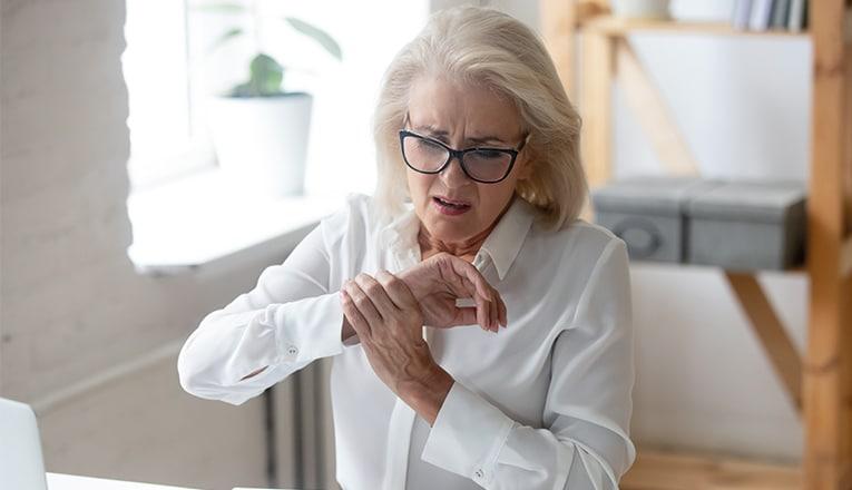 Mevrouw houdt haar pols met ALS klachten vast